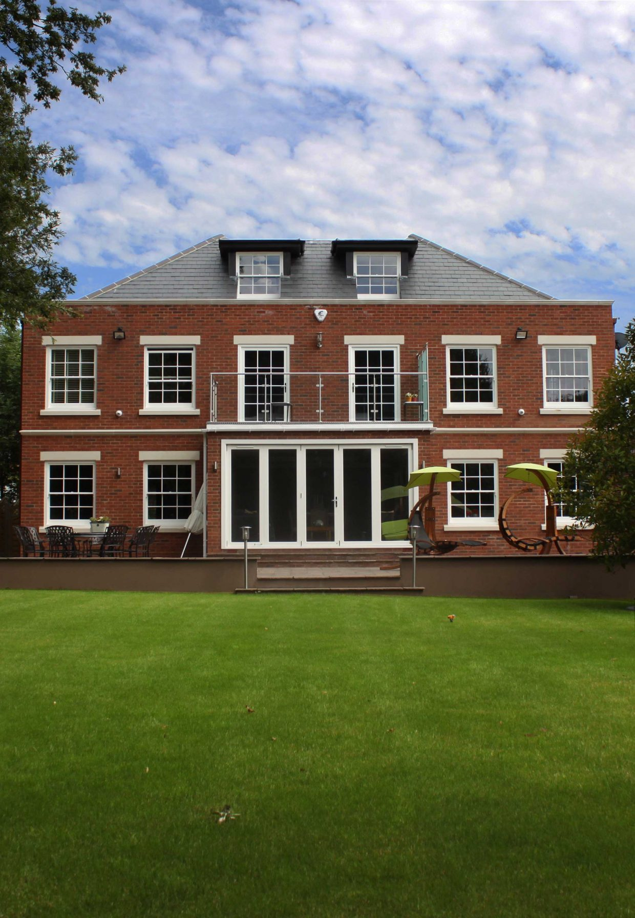 Gallery Image: External shot of rear facade of Chigwell mansion, including Georgian 6 over 6 sash windows and Bifold Doors.
