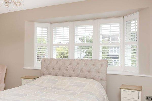 timber casement windows behind guest bed